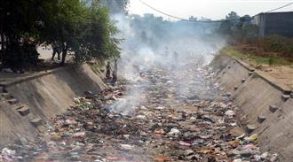 Residents dump waste into canal, set it on fire