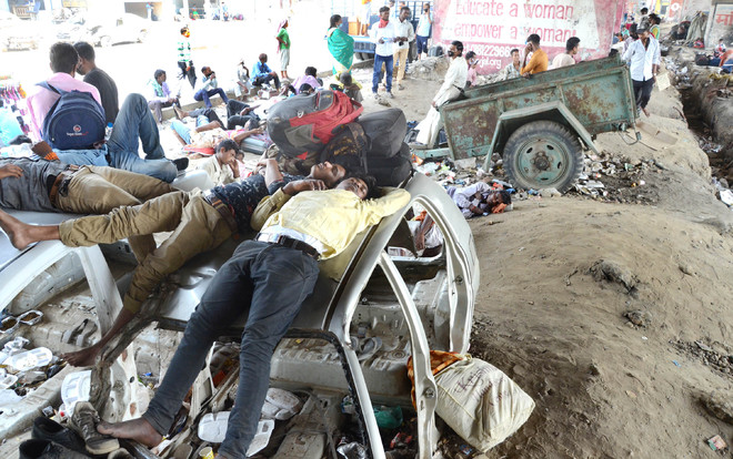 Awaiting nod to board train, migrants camp under flyovers