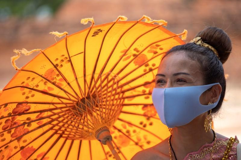 Thais return to temples in traditional garb & masks